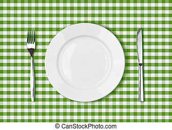 Knife, white plate and fork on green picnic tablecloth