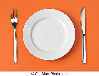 Knife, white plate and fork on orange background