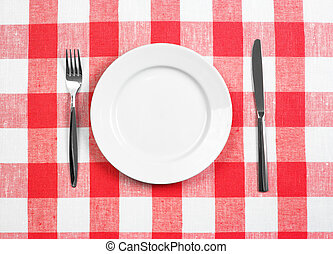 Knife, white plate and fork on red checked tablecloth