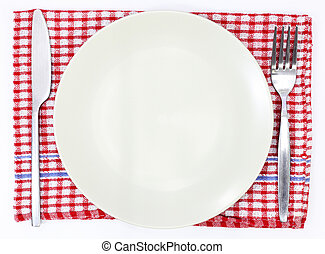 Knife, white plate and fork on red table cloth