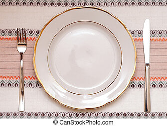 Knife, white plate and fork on tablecloth
