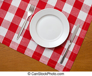 Knife, white plate and fork on wooden table with red checked tablecloth