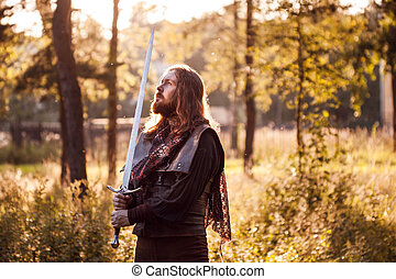 Knight in the forest. A guy in medieval costume with a sword