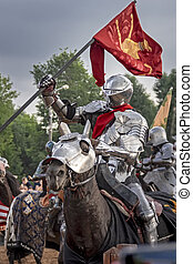 Knight on horseback in medieval steel armor with flag.