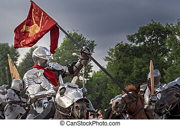 Knight on horseback in medieval steel armor with flag in battle.