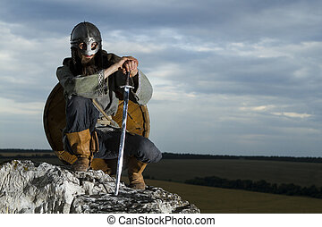 Knight sitting on a rock with a sword against blue cloudy...