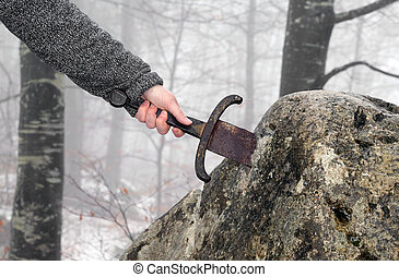 knight tries to remove Excalibur sword in the stone - Hand ...