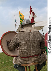 Knight with Helmet and Shield seated on a Chair