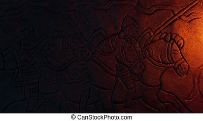 Rock carving of knights on horseback lit up in fire glow