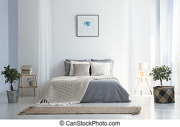 Knit blanket on grey bed in bright bedroom interior with poster and plants. Real photo
