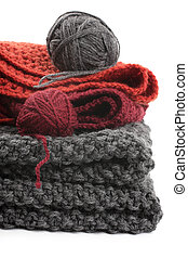 Knits and balls of wool on a white background