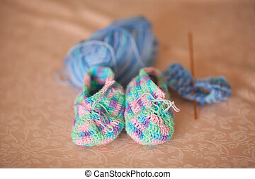 Knitted baby booties on a sofa, hand made