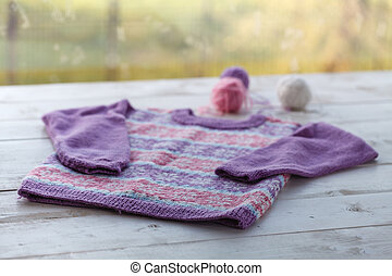 knitted blue sweater for newborn baby on a wooden background