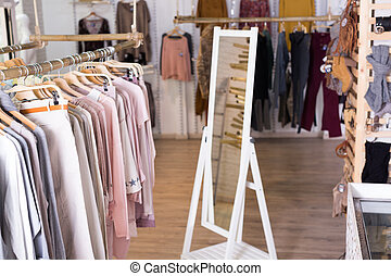 Knitted clothing on hangers in garment store