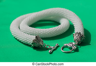 Knitted necklace of white color on a textile background