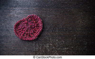 Knitted red heart on a wood background