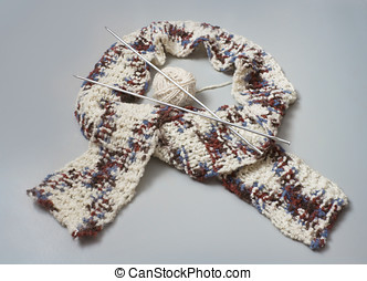 Knitted scarf with knitting needles