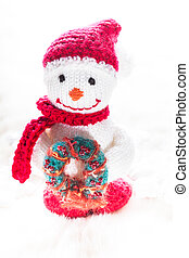 Knitted snowman with christmas wreath on white snow
