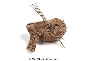 Knitted socks and brown skein of yarn with needles on a white background