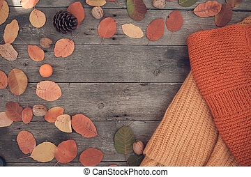 Knitted things and autumn leaves on a wooden background. Top view, rendering, text space. Flat lay.