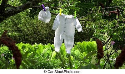 Knitted white baby bodysuit and hat hang on tree branch in garden.
