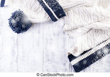 knitted winter scarf and a white cap with a blue strip on a white wooden background. Copy Space for Text Happy New Year Greeting Card Winter Theme