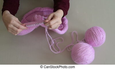Knitting a pink sweater - Close up of female hands knitting...