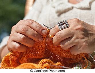 Woman hands doing knitting closeup