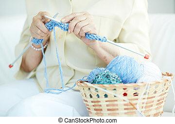 Knitting clothes - Hands of elderly woman knitting woolen...