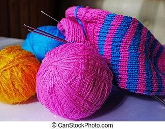 Knitting - Pink, blue and yellow woollen balls,...