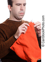 Knitting - A young man is knitting something while sitting...