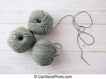 Knitting threads on a dark light wooden background.