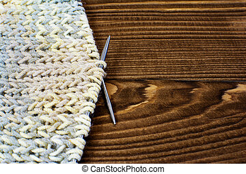 Knitting with knitting needles on wooden background