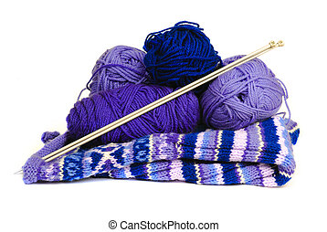 Knitting yarn and needles rest on top of a knitting project, isolated.
