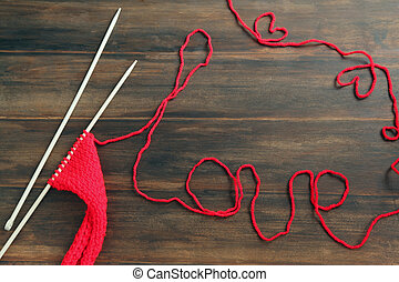 Knitting yarn with word Love on wooden background