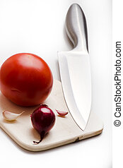 sharp kitchen instruments represented by metallic knives and fresh vegetables