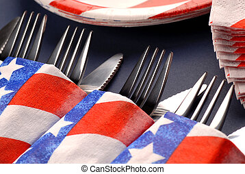 Knives and forks in a 4th of July table setting - Several...