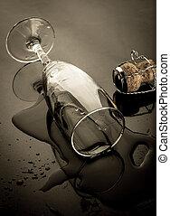 Knocked over champagne flute beside cork on dark backgrounds