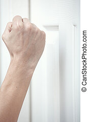 Knocking at the door - Human hand knocking at the wooden...