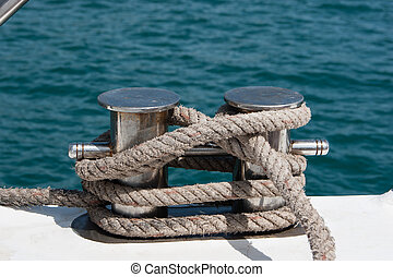 Knot on a bollard of a boat. Blue sea in a background.