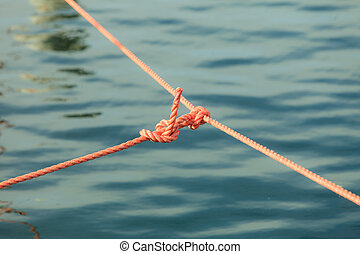 Knot on rope line over sea ocean water.