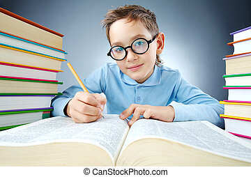 Portrait of cute lad in eyeglasses making notes in book and looking at camera