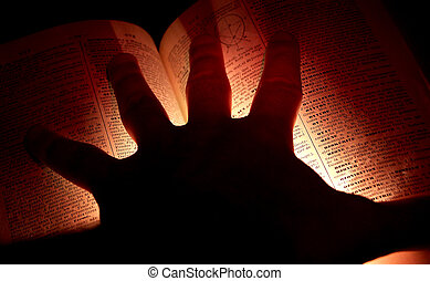 knowledge - hand over an open book illuminated from under...