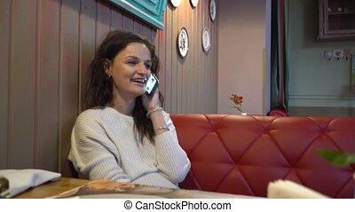 kobieta, aparat fotograficzny., młody, odpoczynek, telefon, spojrzenia, cafe., uśmiechanie się, mówi