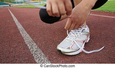 kobieta, biegacz, młody, wiążąc shoelaces