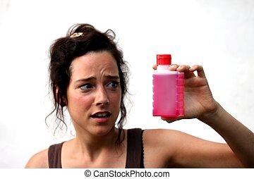 kobieta, młody, płyn, patrząc, krytyczny, butelka, plastyk, czerwony
