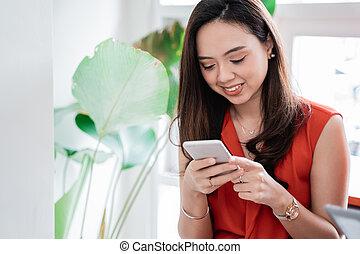 kobieta, młody, smartphone, asian, używając, kawiarnia