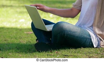 kobieta posiedzenie, na, trawa, jest, używając, niejaki, laptop