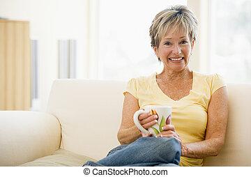 kobieta posiedzenie, w, życie pokój, z, kawa, uśmiechanie...