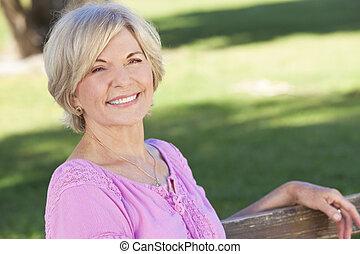 kobieta posiedzenie, zewnątrz, uśmiechanie się, senior,...